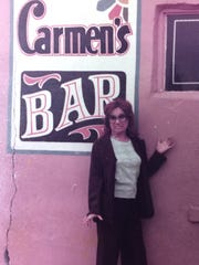 Carmen Ferguson stands by the sign at her bar.