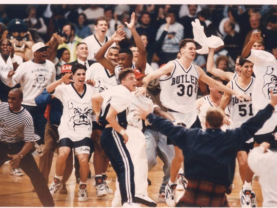 Butler players and fans spill onto the floor in a frenzy after Butler's 75-71 upset of Indiana, Nov. 27, 1993.