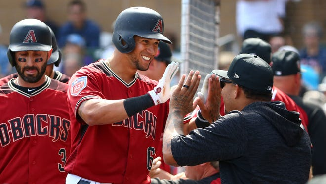 Arizona Diamondbacks David Peralta gets a round of high-fives after hitting a 3-run home run against the Los Angeles Angels in the 3rd inning during spring training action on Mar. 6, 2018 at Salt River Fields at Talking Stick in Scottsdale, Ariz.