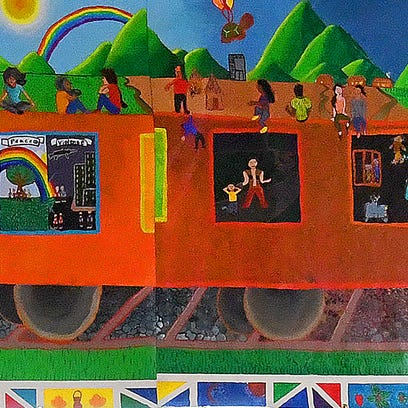 The Train of Dreams mural hangs in the library at Mary