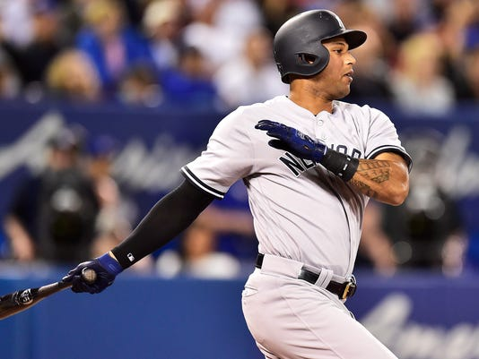New York Yankees' Aaron Hicks follows through on a single against the Toronto Blue Jays during the third inning of a baseball game Thursday, June 1, 2017, in Toronto. (Frank Gunn/The Canadian Press via AP)