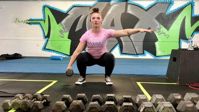 Amanda Krienke, 27, of Maximum Performance Training, 106 S. Madison St., Rockford, demonstrates a suitcase squat on Monday for participants in an online training session. On Friday, health and fitness centers in Illinois will be allowed to reopen with capacity restrictions after being closed for months because of the novel coronavirus.