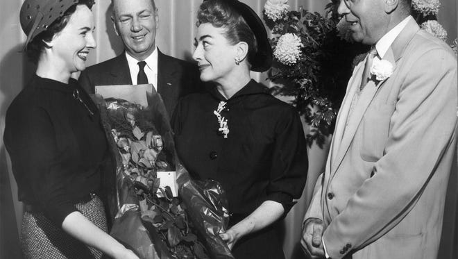 """Actress Joan Crawford (center) made a hit with all who met her while she was in Memphis on November 4, 1955 publicizing her new film, """"Queen Bee"""", at the Warner Theater.  Barbara Walker Hummel (left), Miss America 1947, gave her roses at a press breakfast as Norman Colquhoun (second left) and Eli H. Arkin (right) beamed.  The men are Memphis movie executives."""