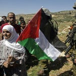 A Palestinian woman holds a Palestinian flag during a protest against the expansion of the Elon Moreh Israeli settlement in the village of Salem near Nablus on the West Bank, Friday, as an Israeli solider looks on.