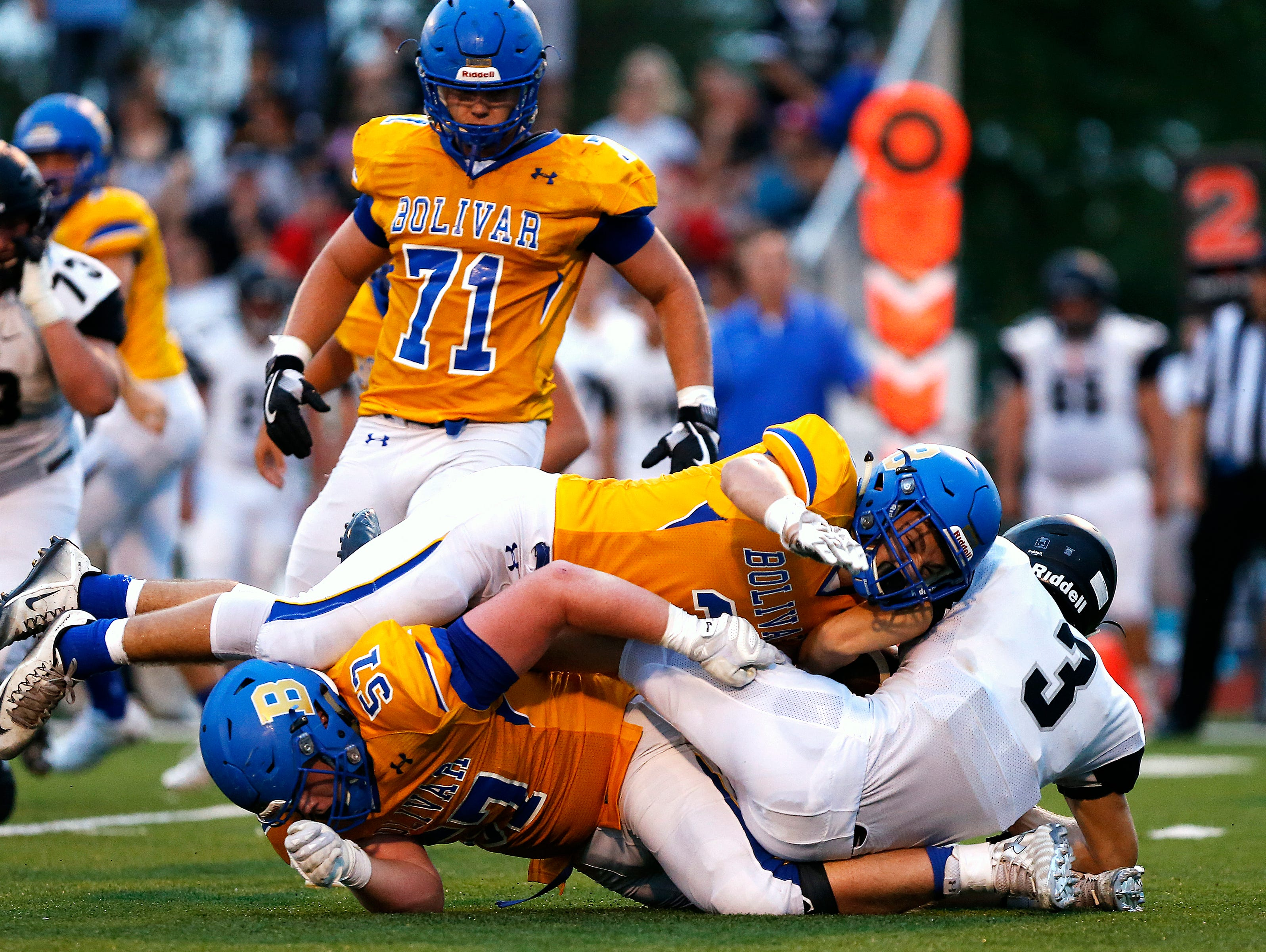Willard High School running back Brock Howard (3) is tackled by Liberators lineman Zach Howard (57) and linebacker Bradley Thomas (3) during first quarter action of the Liberators' football game against Willard High School held at Plaster Stadium in Bolivar, Mo. on Aug. 26, 2016.
