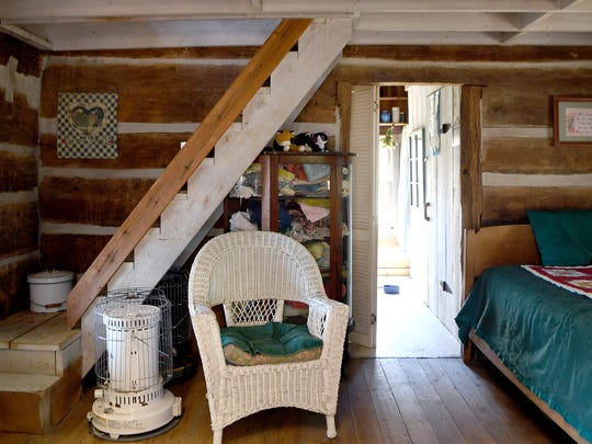 A staircase leads to the loft of the one-room cabin built in 1888 that the Floyds call home. A bed in the loft allows for a place for guests to sleep.