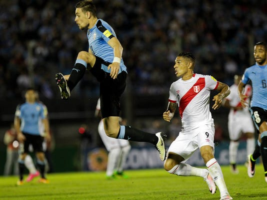 Uruguay's Sebastian Coates, left, fights for the ball with  Peru's Paolo Guerrero during a 2018 Russia World Cup qualifying soccer match in Montevideo, Uruguay, Tuesday, March 29, 2016. (AP Photo/Matilde Campodonico)