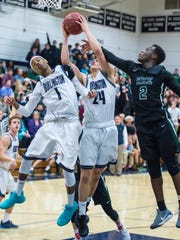 Burlington's Kevin Garrison, center, pulls down a rebound against Rice Memorial's Michel Ndayishimiyeg as James Taylor, left, tries to get out of the way in Burlington on Thursday, December 21, 2017.