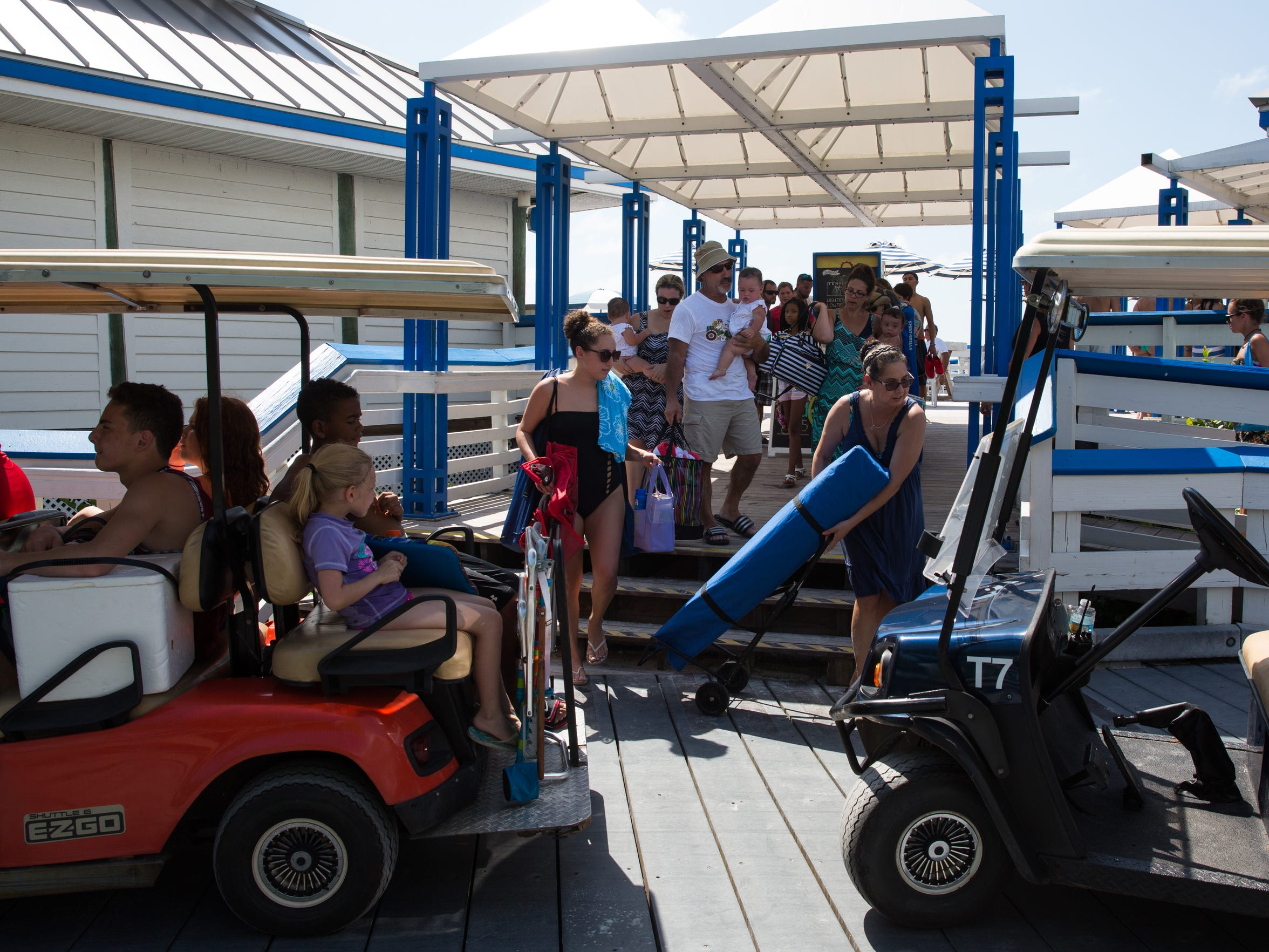 Beachgoers carry their belongings to the tram at the Clam Pass Park beach access point in Naples, Florida on Saturday, Sept. 10, 2016. Clam Pass Park has 171 public parking spaces, which are $8 or free to visitors who have a beach parking sticker.