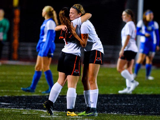 Northeastern's Brittany Arentz hugs teammate Maddie Kling after taking the opening kickoff of the game against Spring Grove on Senior Night, Thursday, Oct. 12, 2017. After being sidelined with a torn ACL before the start of the regular season, the Senior Night game is the only time Arentz took part in a competitive game this season for the Bobcats. John A. Pavoncello photo