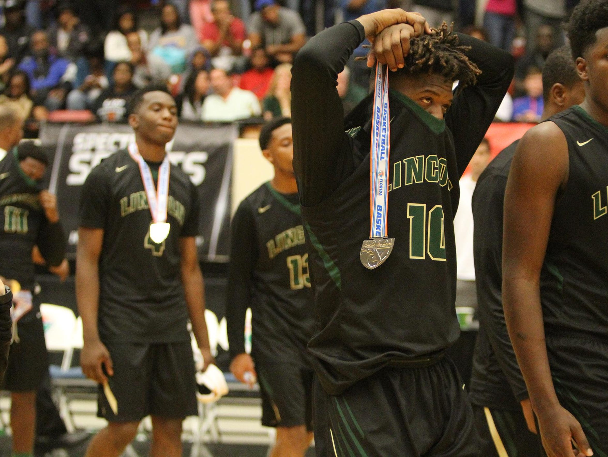 Lincoln's Tyler Farmer (10) reacts after accepting