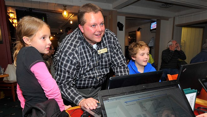 72nd Assembly District race incumbent state Rep. Scott Krug, R-Rome, center, smiles Tuesday while looking at 2012 election results with his children, Ali, left, and Dylan at The Ridges Golf Course, Grand Rapids.