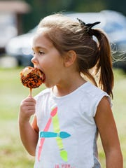 Paige Zortman, 5, of Mequon enjoys a caramel apple during Applefest at Thiensville Village Park on Sunday, Oct. 1, 2017. The event, hosted by the Thiensville-Mequon Lions Club, is a celebration of the autumn harvest and Ozaukee County's apple heritage.