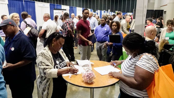 Jobseekers fill out applications during the Lafayette Economic Development Authority (LEDA) Job Fair at the Cajundome Convention Center Tuesday, May 9, 2017.