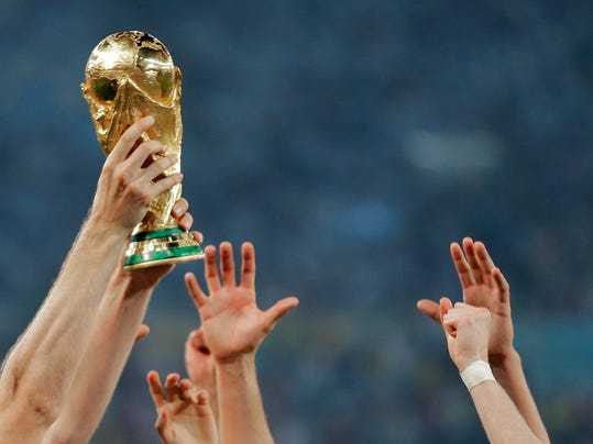FILE - In this Sunday, July 13, 2014 file photo, German players reach out to touch the trophy after the World Cup final soccer match between Germany and Argentina at the Maracana Stadium in Rio de Janeiro, Brazil. The Morocco 2026 World Cup bid has presented scarce details with six months until the vote, it was reported Friday, Jan. 12, 2018. (AP Photo/Matthias Schrader, File)