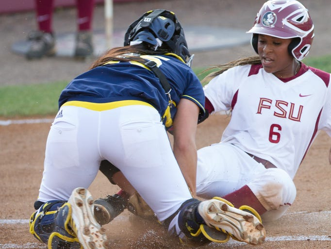 FSU's Tiffani Brown (6) slides into Michigan catcher Lauren Sweet (25) in an unsuccessful attempt to reach home plate during the FSU vs. Michigan NCAA Super Regional softball game on Thursday, May 22, 2014 in Tallahassee, Fla.