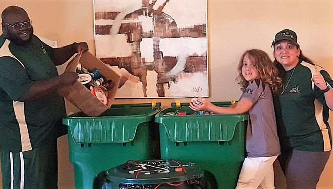 Suntree-Viera Youth Football League board member Stafford Slaughter, player Noah McMinis and his mother and board member Stephanie Valletta show off some of the plastic lids they've collected for their bench project.