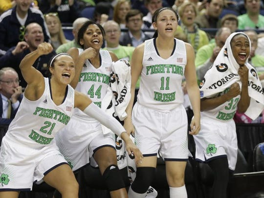 Notre Dame players, from left, Kayla McBride, Ariel Braker, Natalie Achonwa, and Jewell Loyd, cheer a teammate's basket against North Carolina State during the second half of an NCAA college basketball semifinal game at the Atlantic Coast Conference tournament in Greensboro, N.C., Saturday, March 8, 2014. Notre Dame won 83-48. (AP Photo/Chuck Burton)