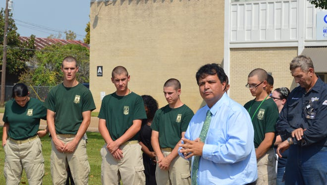 Central Louisiana Technical Community College Chancellor Jimmy Sawtelle addresses students who gather around the school's flagpole for a moment of silence Thursday in honor of victims of the Oct. 1 shooting at a community college in Oregon.
