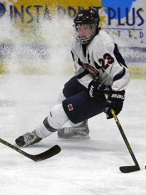 Trenton Bliss of Appleton United looks to control the puck against Fond du Lac Springs in boys' hockey at the Appleton Family Ice Center in Appleton on Thursday, January 15, 2015.