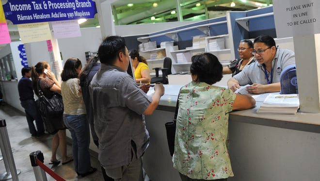 Tax Service Specialist Antonette Donato, right, assists a customer in filing a tax return at the Department of Revenue and Taxation in Barrigada Heights in April 2013.
