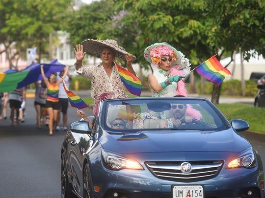 """Chamorro historian Toni """"Malia"""" Ramirez, top left, waves while participating in Guam's second LGBTQ pride march in Tumon on June 2, 2018."""