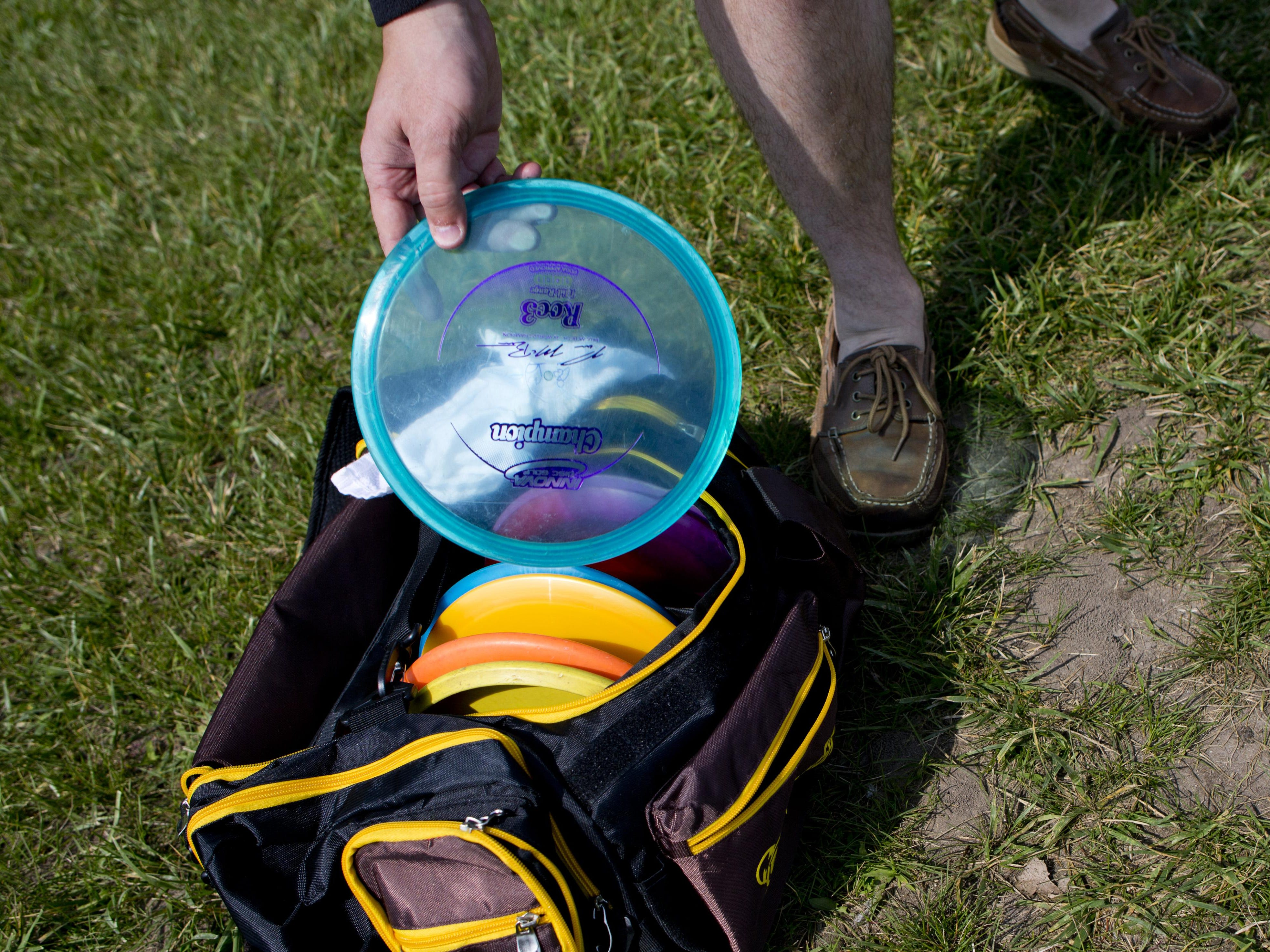 Paul Costanzo grabs a disc while playing disc golf Friday, July 3, 2015 at Holland Woods in Port Huron.