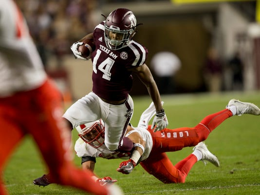 Texas A&M wide receiver Camron Buckley (14) avoids a tackle by New Mexico safety Jacob Girgle (16) after a catch and runs during the first quarter of an NCAA college football game on Saturday, Nov. 11, 2017, in College Station, Texas. (AP Photo/Sam Craft)