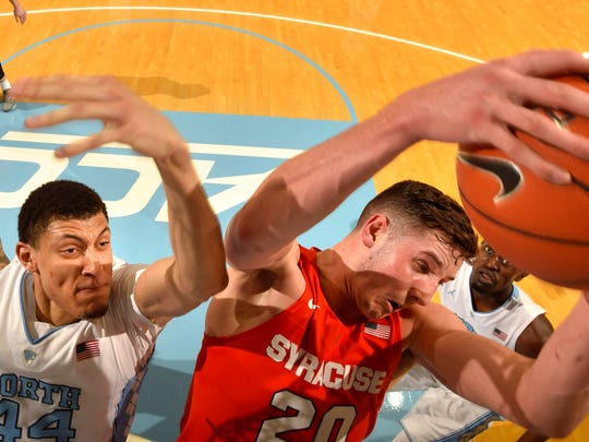 Syracuse's Tyler Lydon grabs a rebound as North Carolina's Justin Jackson swipes for the ball on Feb. 29 in Chapel Hill, North Carolina.