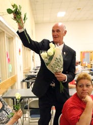 John Cook, candidate for County Judge gives out roses