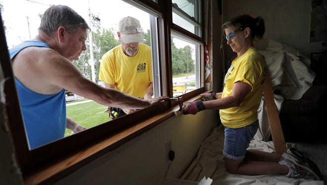 Homeowner Lee Catron, left, helps volunteers Keith Glass and Mary Jo Glass replace a window July 18, 2017 during the Habitat for Humanity Rock the Block program on Doty Island. This year, the effort will focus on 100 homes in Menasha.