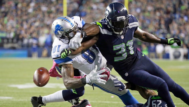Seattle Seahawks strong safety Kam Chancellor (31) knocks the ball loose from Detroit Lions wide receiver Calvin Johnson (81) in the second half of an NFL football game, Monday, Oct. 5, 2015, in Seattle. The fumble went out of bounds in the end zone and was ruled a touchback. The Seahawks beat the Lions 13-10.