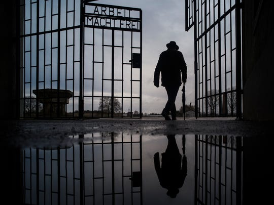 A man walks through the gate of the Sachsenhausen Nazi death camp the phrase 'Arbeit macht frei' (work sets you free) at the International Holocaust Remembrance Day, in Oranienburg, about 18 miles north of Berlin, Germany, Sunday, Jan. 27, 2019. The International Holocaust Remembrance Day marks the liberation of the Auschwitz Nazi death camp on Jan. 27, 1945.