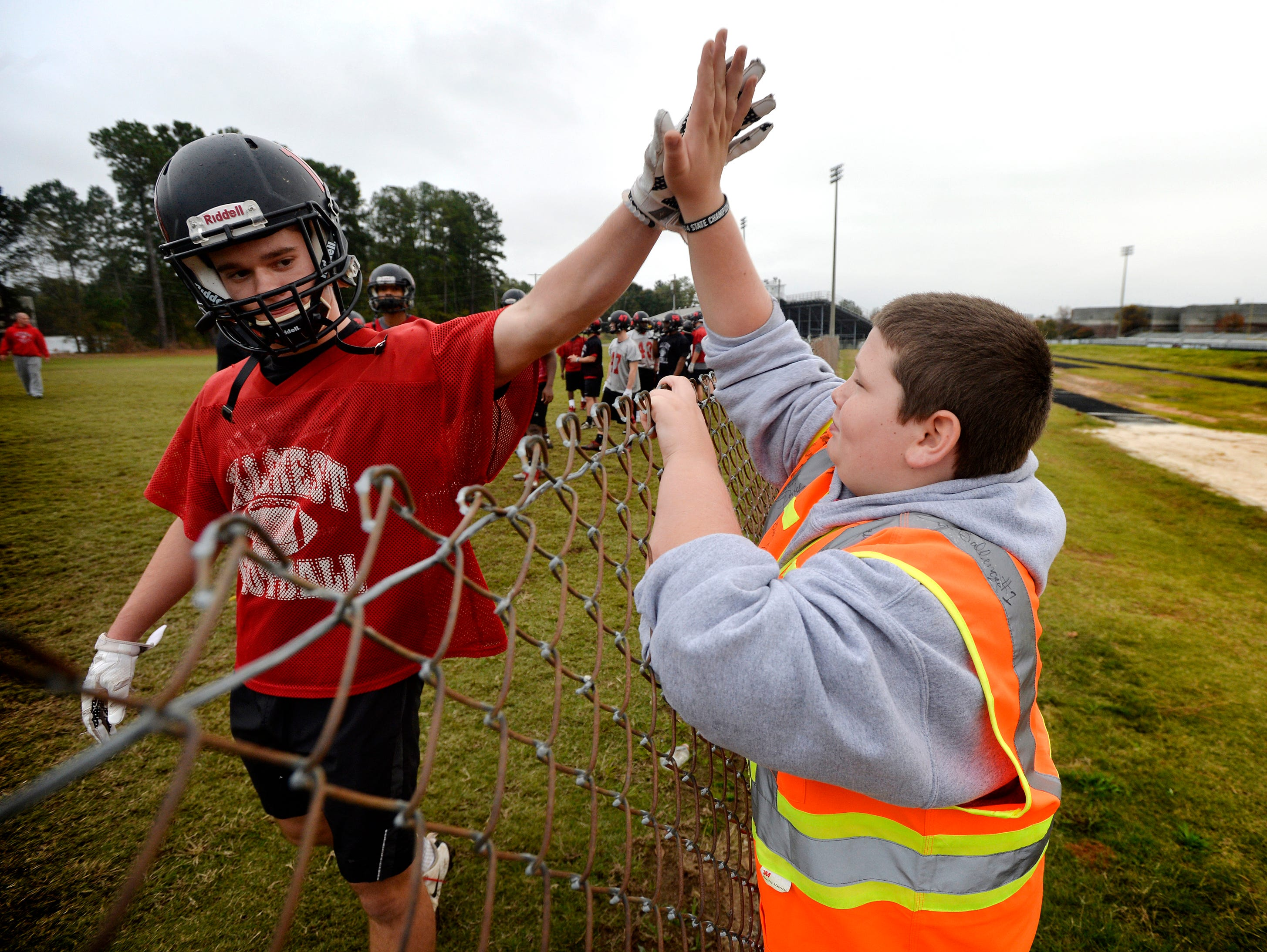 Hillcrest's Garrett Savage (18) high-fives 11-year-old Andrew Pepper as he watches the Hillcrest High School Rams practice on Nov. 5, 2015. Pepper rides his bike to every Rams football game.