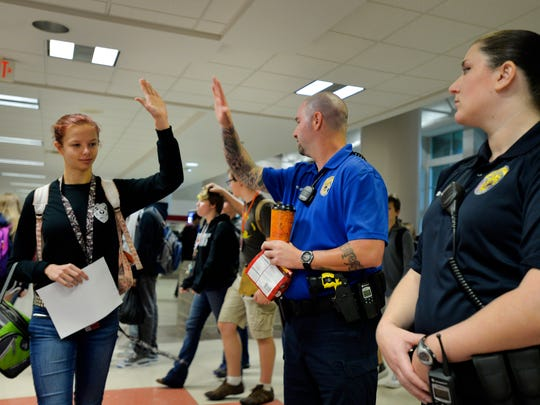A student gives Tony Koutsos, a school resource officer at Mauldin High School, a high-five before classes start on Nov. 6, 2015.