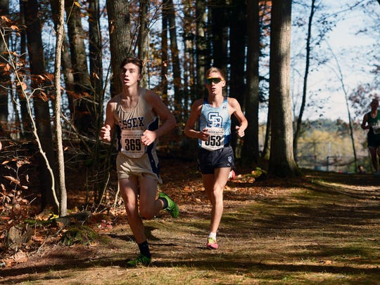 Lucas Calcagni of South Burlington, right, stalks Henry Farrington of Essex at the mid-point of the Division I boys race at the Vermont Cross Country Championships at Thetford Academy last year.