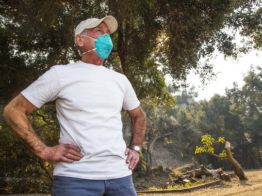 Bill Hahn, owner of the Rose Story Farm, stands his ground at his 15-acre property, hoping that firefighters can save his property in Carpinteria, Calif.