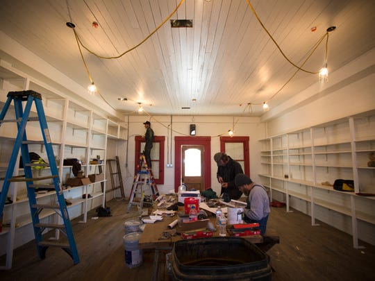 "Thu., Feb. 2, 2017: The interior of the restored Rabbit Hash General Store as some of the final touches ÐÊshelves and lighting ÐÊare added. ""It looks like it did the day before it burned, except it looks like it's got a fresh coat of paint on it,"" said Don Clare, president of the Rabbit Hash Historical Society. Ed Unterreiner, owner of Rivertown Construction who headed the construction, is pictured, front."