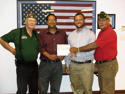 From left, Quarter Master Allan Kuchinksky, VFW Post 7686; Alamogordo Tiger band Director Sham Al-Masoud; Alamogordo Tiger Band Director Rod Pior; and Commander Art Sanchez, VFW Post 7686. Sanchez and Kuchinsky present the band directors with a 1,000 donation to the Alamogordo High School Tiger Band to repair and buy new equipment.