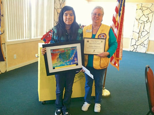 Kitty Callender represented the Lions Club and several other non profits, serving in many capacities. She is seen here presenting an award for a Peace Poster contest.