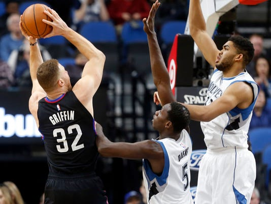 Los Angeles Clippers' Blake Griffin, left, shoots as Minnesota Timberwolves' Gorgui Dieng of Senegal and Karl-Anthony Towns, right defend during the first half of an NBA basketball game Wednesday, March 8, 2017, in Minneapolis. (AP Photo/Jim Mone)