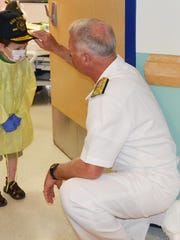 Keesville, N.Y., resident Liam MacDougal receives a USS Carney hat from Navy Vice Adm. Tom Rowden at the University of Vermont Children's Hospital.