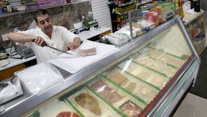 Wafik Altaweel with his case of  hand made cured meats being offered at the Old World Meat Market.  Altaweel wants to recreate what the old Hartmann's meat market used to offer the neighborhood.