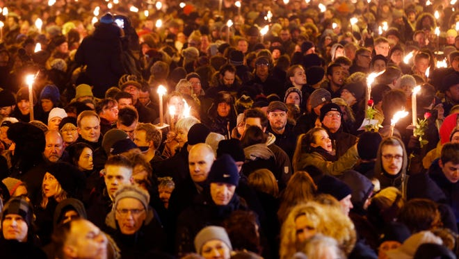 Hundreds of people gather for a vigil near the cultural club in Copenhagen, Denmark, Monday, Feb. 16, 2015. The slain gunman behind two deadly shooting attacks in Copenhagen was released from jail just two weeks ago and might have become radicalized there last summer, a source close to the Danish terror investigation told The Associated Press on Monday.