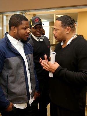 Detroit Cass Tech football coach Thomas Wilcher, right, talks with Mike Weber before Weber committed to Ohio State on Wednesday, Feb. 4, 2015, in Detroit.