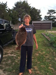 Brock Hilligoss proudly displays his 20-inch flounder