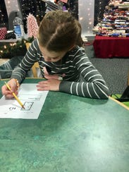 Eight-year-old Erica Koerner works through a maze using