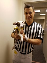 Dan Schachner, the Puppy Bowl ref, holds Dakota in