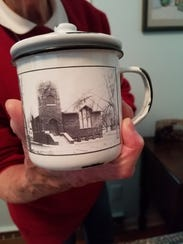 Beverly Franzke proudly shows off a mug with a picture