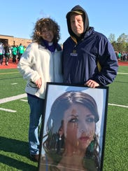 Kathy and Bob Landenberger with a portrait of daughter